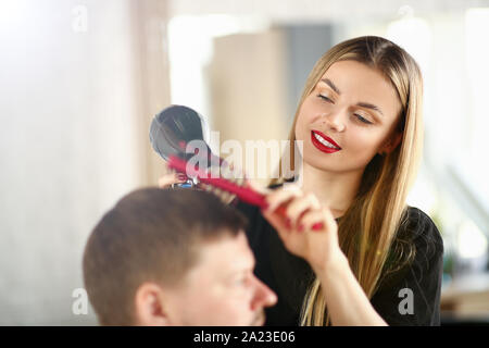 Young Girl Hairdresser Holding Dryer and Hairbrush - Stock Photo