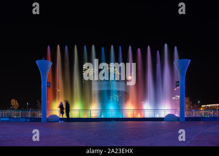 Brightly lit fountain in the evening im Minsk, Belarus. There is a National Library of Belarus behind it. - Stock Photo