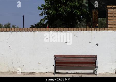 A wooden bench where you can sit with an old wall in the background and some trees from a small park nearby - Stock Photo