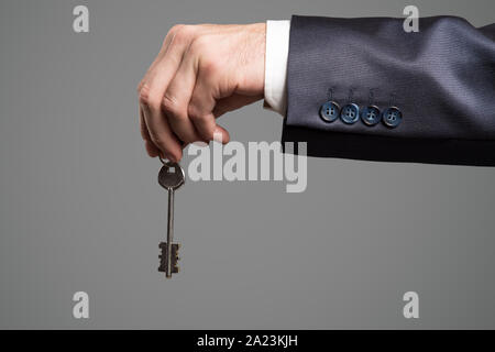 Man in the suit holding key in hand. - Stock Photo