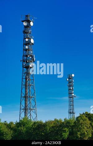 two telecommunication masts TV antennas wireless technology against blue cloudless sky over green hedges - Stock Photo