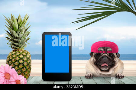 smiling tropical summer pug dog with cap and tablet, with paws on vintage green wooden table and sea and beach on background - Stock Photo