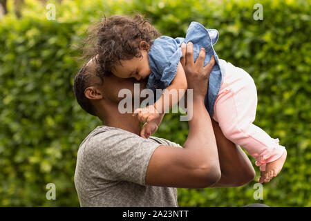 Father holding his little girl. Mixed race family.
