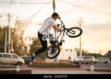The guy on the BMX, performing a trick, jumps up from the parapet.