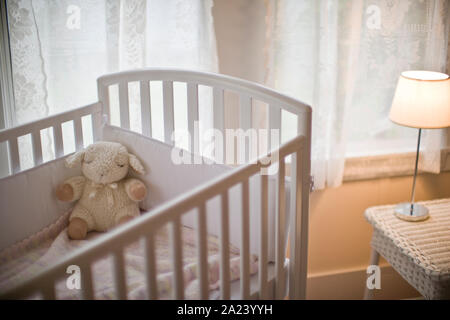 Soft toy in a cot inside an empty nursery. - Stock Photo