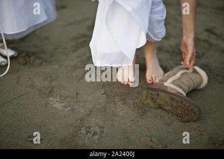 Bare feet standing in sand next to a warm sheepskin boot. - Stock Photo