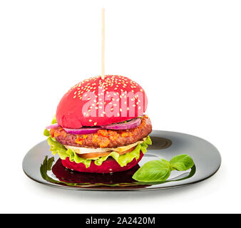 Vegan burger with soy and seitan meat, tofu and vegetables, red bun, served on a plate - Stock Photo