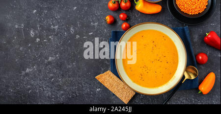 Vegan winter cream soup with red lentils on black background. Long banner. Copy space - Stock Photo