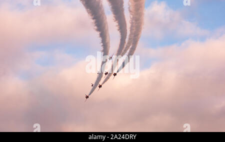 Jets fly in formation against a pink sky over Vancouver Harbor - Stock Photo