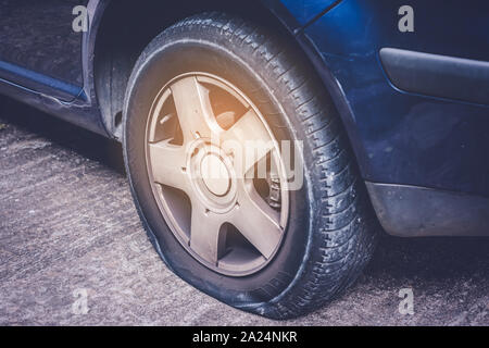 Closeup of a flat tire on car - tire change concept - Stock Photo