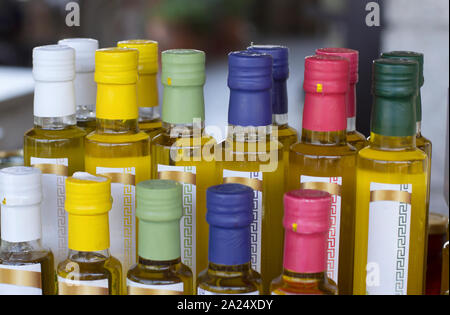Glass olive oil bottles without trademark with colorful sealed stoppers and greek ornament on blurred background closeup - Stock Photo