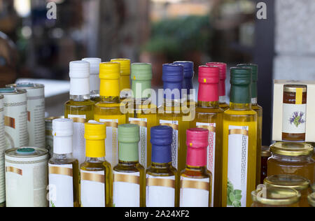 Glass olive oil bottles without trademark with colorful sealed stoppers and greek ornament on blurred background - Stock Photo