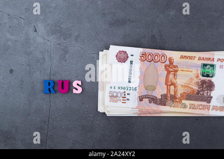 Big stack of Russian money banknotes of five thousand rubles lying on a grey cement background - Stock Photo