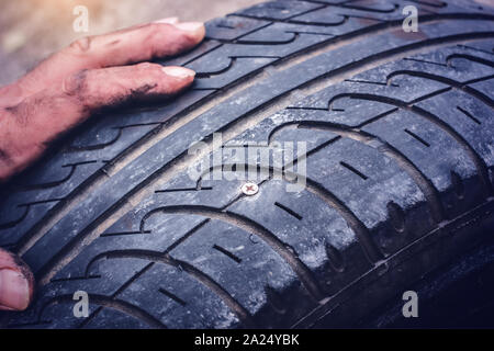 Hands on flat car tire punctured with a screw closeup - - Stock Photo