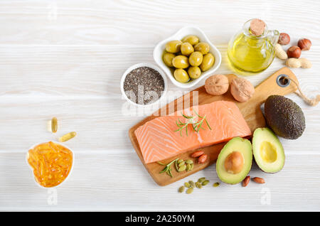 Selection of healthy unsaturated fats, omega 3 - fish, avocado, olives, nuts and seeds. - Stock Photo