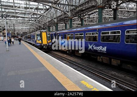 Passengers boarding Scotrail Class 380 Desiro electric trains at Glasgow Central Station - Stock Photo
