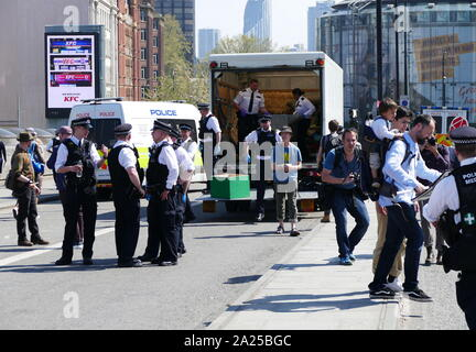 Police remove obstructive furniture as Extinction Rebellion climate change protesters protest peacefully, by occupying Waterloo Bridge, in London. April 20th 2019 - Stock Photo