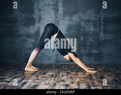 young attractive woman in adho mukha svanasana pose