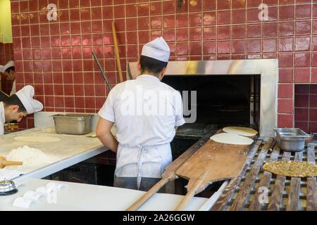Chef at work, man preparing lahmacun. Traditional Turkish Food aka Turkish Pizza. - Stock Photo