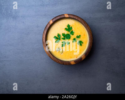 Vegetable soup decorated parsley and pumpkin seeds in oak wooden bowl on grey concrete background, copy space - Stock Photo