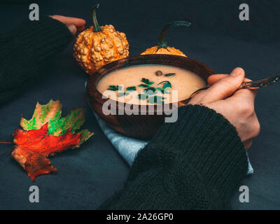 female hands and Fall warming pumpkin cream soup with croutons and seeds Autumn vegetarian, vegan, healthy comfort food eating concept - Stock Photo