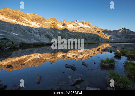 Peaks reflected on alpine lake. Reichenspitzgruppe. Reichenspitze peak. Sunrise sunlight on peaks and glaciers. Hohe Tauern Nationalpark. - Stock Photo