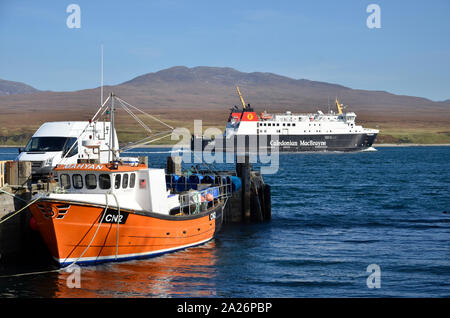 MV Finlaggan, a Caledonian MacBrayne island ferry at Port Askaig on the Scottish Island of Islay. The hills of Jura can be seen in the background. - Stock Photo