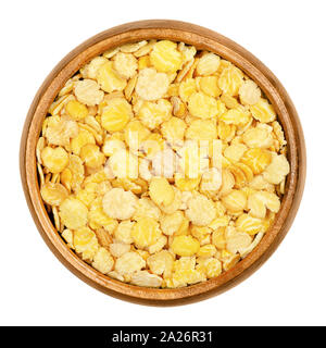 Soya flakes in wooden bowl. Defatted and toasted soybeans, rolled into flakes. Glycine max, also known as soya bean, a legume and oilseed. - Stock Photo