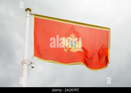 flag of Montenegro, on a flagstuff in front of the sky - Stock Photo