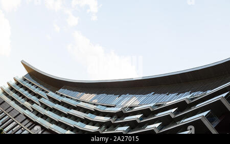Bottom view of modern glass building with hollow roof against clear blue sky - Stock Photo