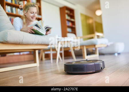 Vacuum robot automatically cleans parquet floor with housewife in the background - Stock Photo