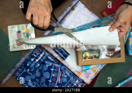 Female hands with scissors cutting wrapping paper for christmas gifts, overhead close-up - Stock Photo