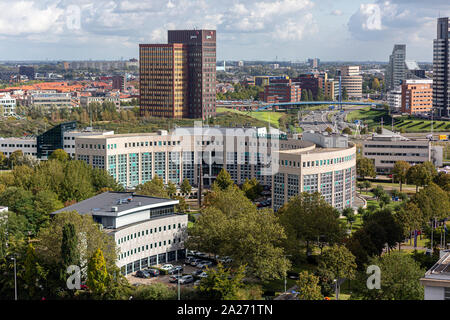 City view of Rotterdam with high rise and low rise buildings in a green environment with a modern office building in the foreground - Stock Photo