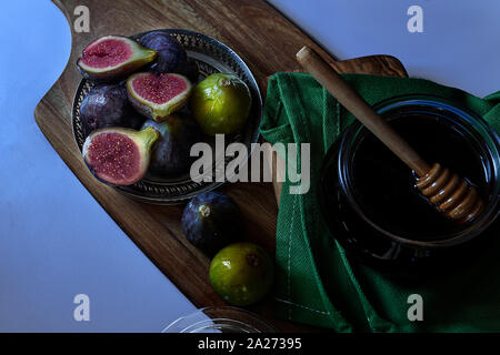 Top view. Fresh purple and green figs on a metal bowl and accompanied by a jar of honey. Blue background, - Stock Photo