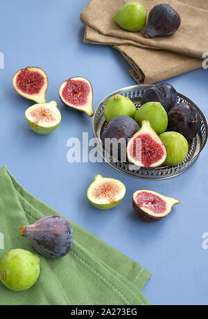 Fresh purple and green figs on a metal bowl and on a blue background. - Stock Photo