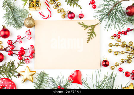 Christmas composition. Vintage paper background with copy space and red holly berries, golden stars and green fir branch on white - Stock Photo