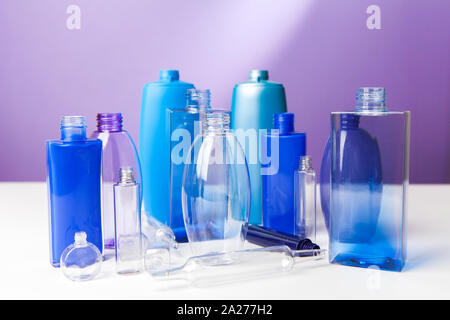 Group of empty plastic bottles, ampouls and vials,  of various sizes and colors. On purple background - Stock Photo