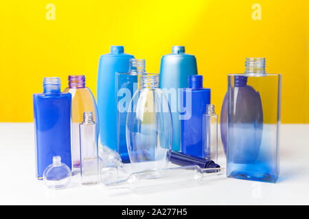 Group of empty plastic bottles, ampouls and vials,  of various sizes and colors. On yellow background - Stock Photo