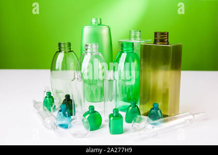 Group of empty plastic bottles, ampouls and vials,  of various sizes and colors. On green background - Stock Photo