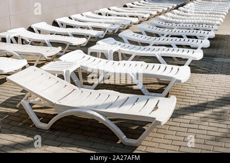 White plastic sunbeds under the sun on the tiles by the pool. low season at the resort. there are no tourists on the beach. The holiday season ends. c - Stock Photo