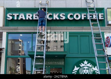 South Korea: Worker cleans Starbucks sign at a location in central Seoul.Photo from 10. September 2018. | usage worldwide - Stock Photo
