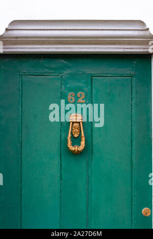Wooden front door in green with the number 62 - Stock Photo