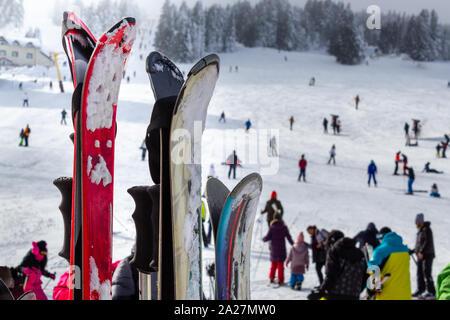 Ski touring equipment. Snow skis and people skiing in the ski resort. Winter ski season on mountain - Stock Photo