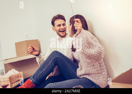 Cheerful man and his beautiful girlfriend sitting on the floor with sparklers in their hands - Stock Photo