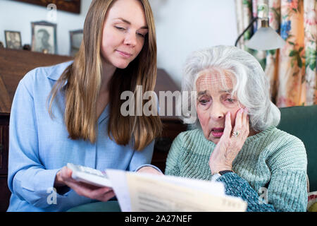 Woman Helping Worried Senior Neighbor Concerned About Debt With Bills And Paperwork