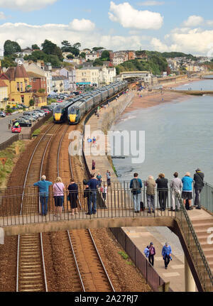 Great Western Intercity Express trains passing at Dawlish, watched by people on a footbridge. - Stock Photo