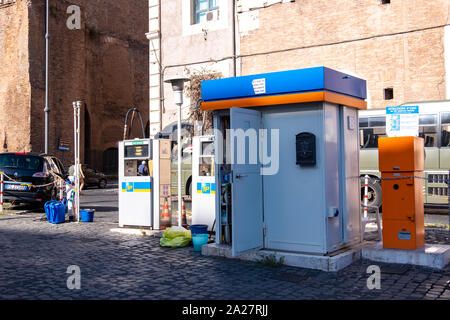 Tiny three pump fuel garage with miniature office, facing onto narrow cobble street, central Rome on the Piazza Della Republica right beside a cafe - Stock Photo