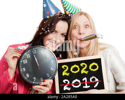 Two women holding a chalkboard and a clock isolated on white background. New year 2020 concept. - Stock Photo