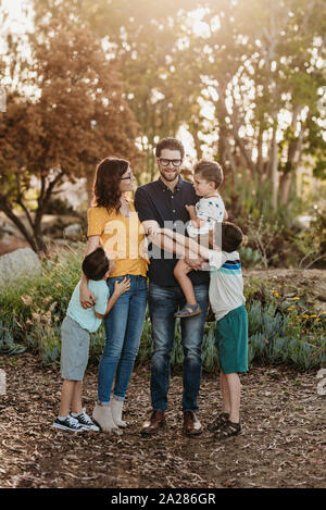 Portrait of family smiling at each other and hugging in cactus garden - Stock Photo