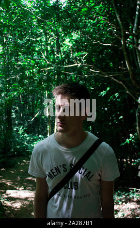 young boy surrounded by greenery with many shadows of tree branches - Stock Photo